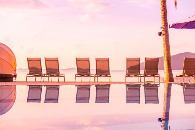 Hermosa vista al aire libre con sombrilla y silla alrededor de la piscina en hotel de lujo y resort