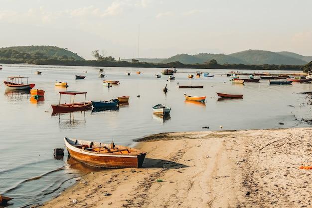 Hermosa vista de una bahía con barcos de pesca cerca de una orilla arenosa