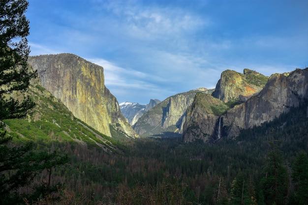 Hermosa vista de una cascada que fluye de una roca y se vierte en el magnífico paisaje verde