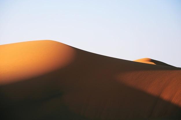 Hermosa vista de un desierto durante la puesta de sol bajo un cielo azul claro