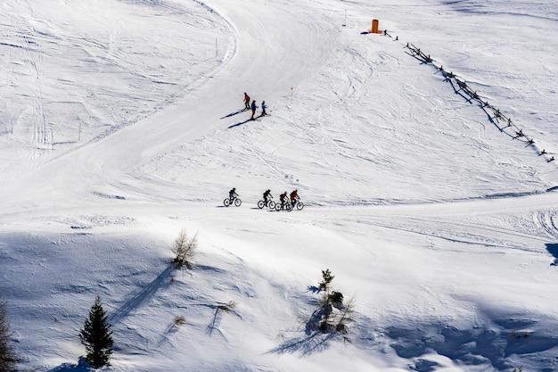Hermosa vista de la gente en bicicleta y esquiar a través de montañas nevadas en el tirol del sur, dolomitas, italia