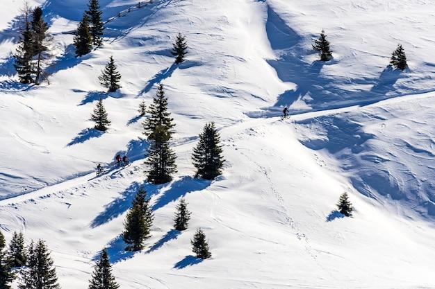 Hermosa vista de la gente en bicicleta a través de montañas nevadas en el tirol del sur, dolomitas, italia