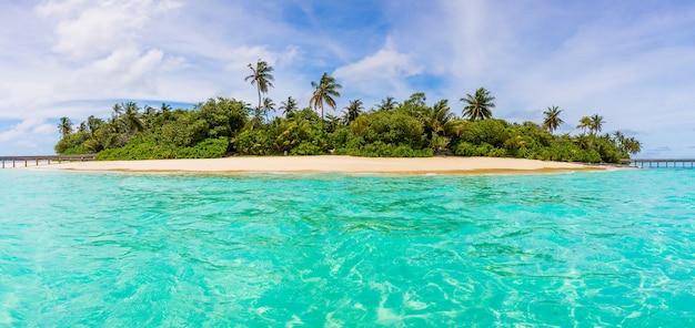 Hermosa vista de una isla con un espeso bosque desde el agua en las maldivas en un día soleado