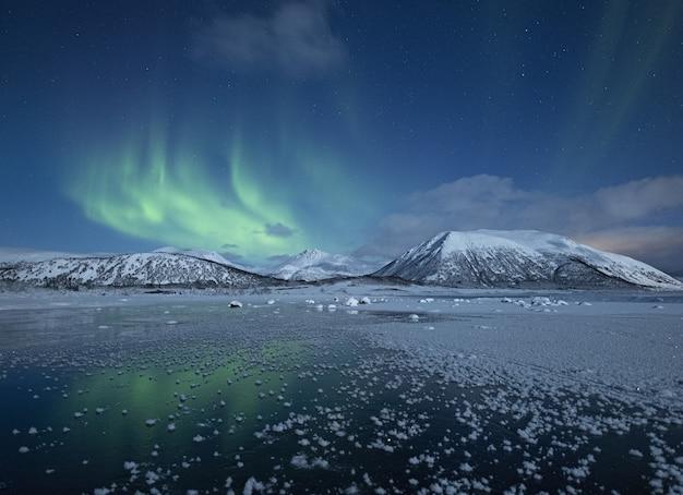 Hermosa vista del lago medio congelado rodeado de colinas cubiertas de nieve bajo la aurora boreal