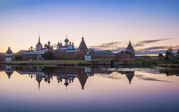 Una hermosa vista del monasterio solovetsky con una imagen de espejo en el agua de la bahía blagopoluchiya en las islas solovetsky a la luz de un amanecer otoñal