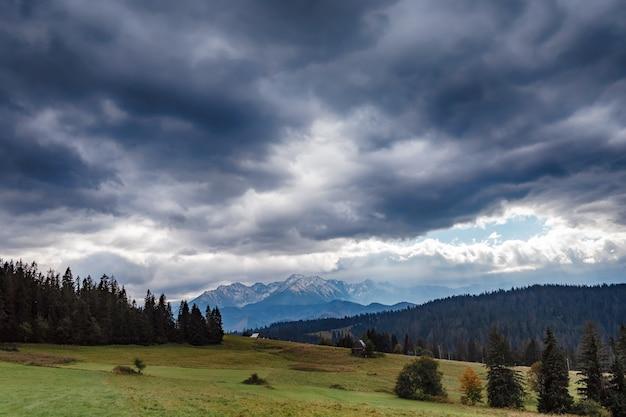 Hermosa vista a la montaña de gran tamaño. día nublado de otoño. el sol intenta atravesar las nubes.