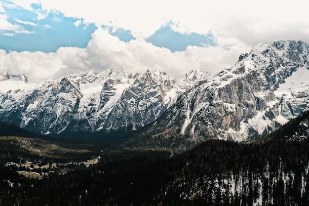 Hermosa vista de montañas cubiertas de nieve con increíble cielo nublado