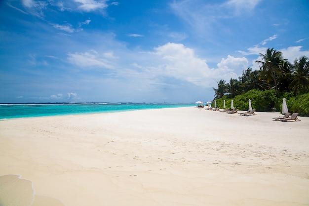 Hermosa vista del océano ondulado golpeando la playa de arena bajo el cielo nublado