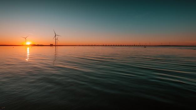 Hermosa vista del océano tranquilo con turbinas bajo la fascinante puesta de sol en el