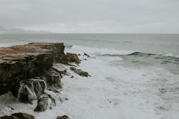 Hermosa vista de las olas espumosas que llegan a la orilla rocosa