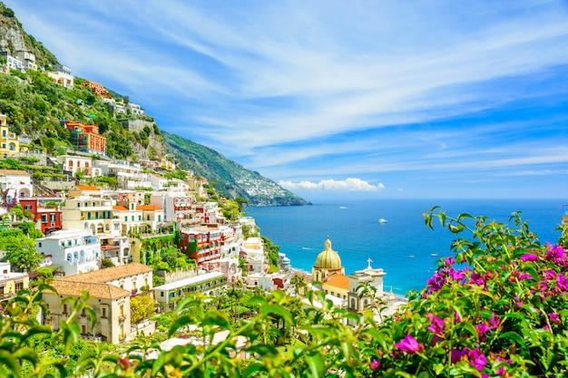 Hermosa vista de positano en la costa de amalfi con flores borrosas en primer plano