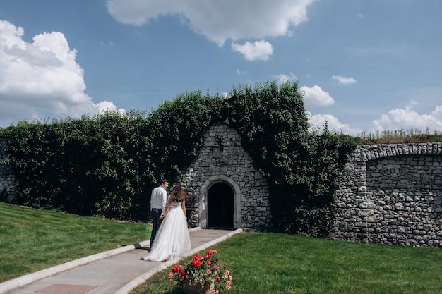 Hermosa vista posterior de una pareja casada frente a la entrada en el muro de piedra al aire libre