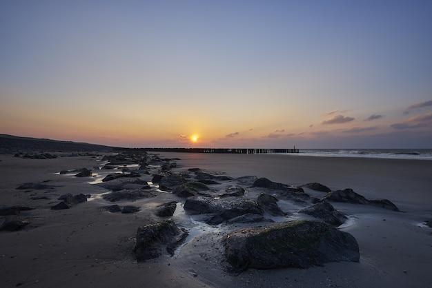 Hermosa vista de la puesta de sol con nubes púrpuras sobre la playa