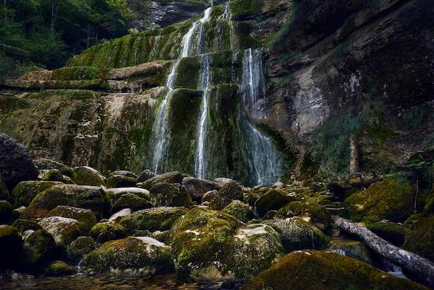 Hermosa vista de las rocas cubiertas de musgo y las cascadas en los acantilados.