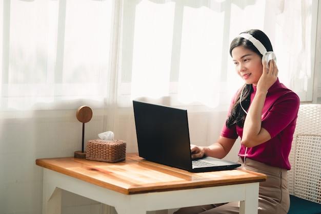 Hermosas alumnas asiáticas con audífonos mientras estudian en línea las maestras y los alumnos usan sistemas de videoconferencia en línea para enseñar a los alumnos.