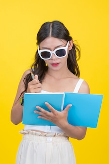 Hermosas alumnas sostienen cuadernos y bolígrafos