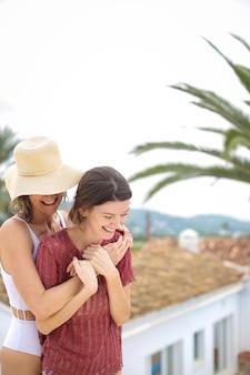 Hermosas amigas abrazándose en una terraza en la azotea