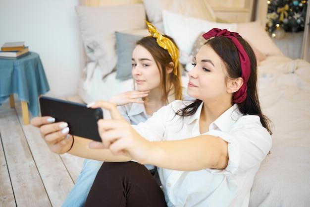 Hermosas amigas jóvenes relajándose en casa juntos tomando selfie