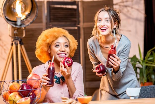 Hermosas amigas multiétnicas sentadas con alimentos y bebidas saludables en el interior en el moderno y acogedor interior de la casa