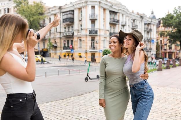 Hermosas amigas tomando fotos en la ciudad