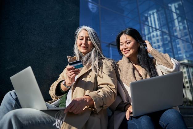 Hermosas amigas usando computadoras portátiles para compras en línea