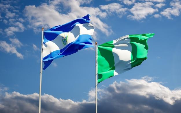 Hermosas banderas del estado nacional de nigeria y el salvador juntos en el cielo azul