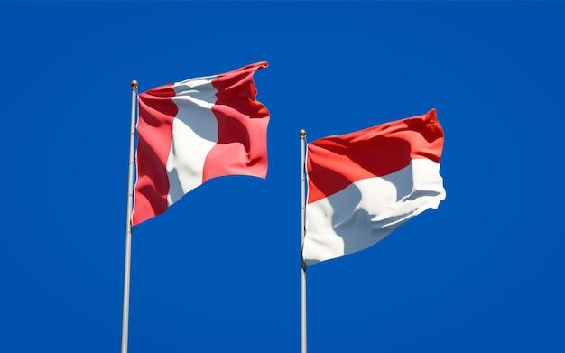 Hermosas banderas del estado nacional de perú e indonesia juntos en el cielo azul