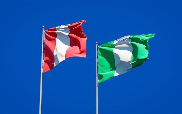 Hermosas banderas del estado nacional de perú y nigeria juntos en el cielo azul