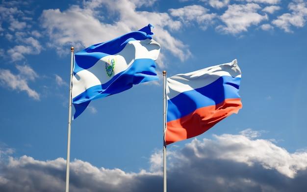 Hermosas banderas del estado nacional de rusia y el salvador juntos en el cielo azul. ilustraciones 3d