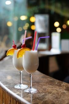 Hermosas bebidas alcohólicas cócteles con piña pinacolada y coco en la barra de la barra