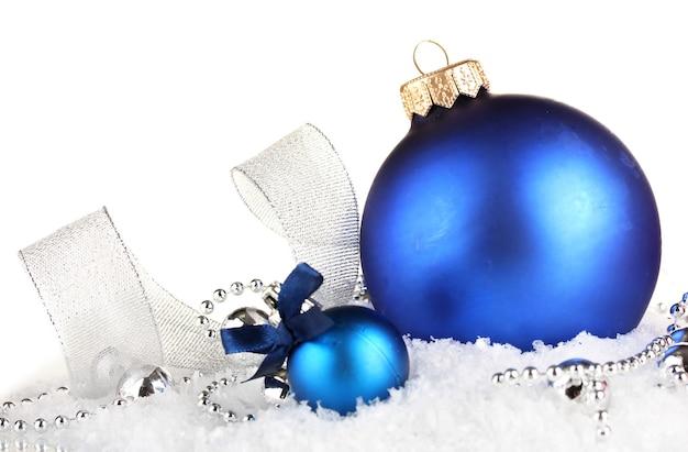Hermosas bolas de navidad azul sobre la nieve, aislado en blanco