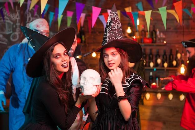 Hermosas brujas jóvenes con grandes sombreros celebrando halloween. médico aterrador en el fondo.
