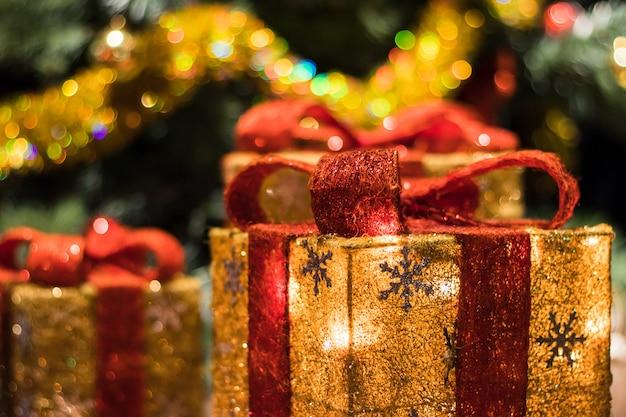 Hermosas cajas decoradas con regalos bajo el árbol de navidad.