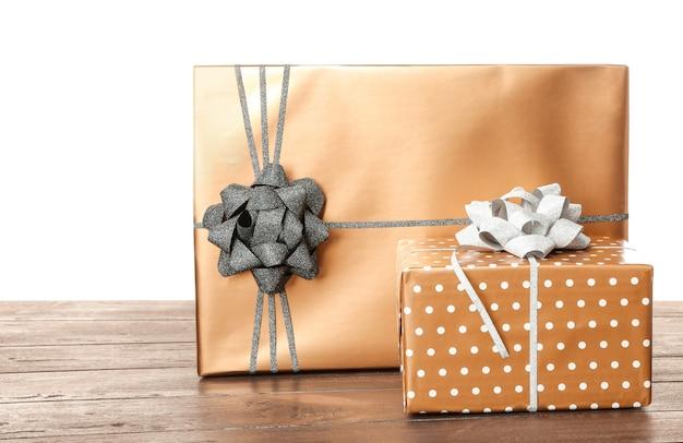 Hermosas cajas de regalo en la mesa contra un blanco