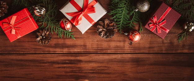Hermosas cajas de regalo, ramas de abeto y bolas de navidad sobre fondo de madera. lugar para el texto.