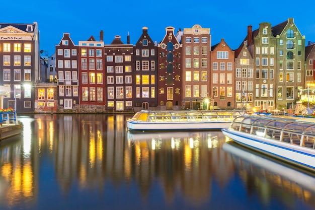 Hermosas casas de baile típicas holandesas y barcos turísticos en el canal damrak de amsterdam en la noche, holanda, países bajos.