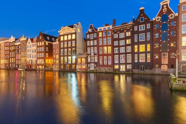 Hermosas casas de baile típico holandés en el canal damrak de amsterdam en la noche, holanda, países bajos.