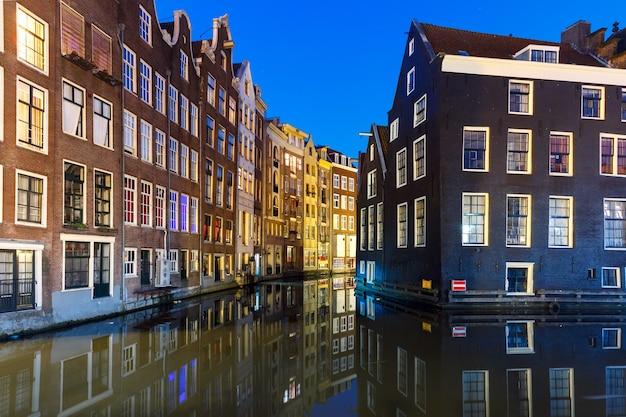 Hermosas casas típicas holandesas en el canal de amsterdam por la noche, holanda, países bajos.