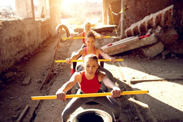 Hermosas chicas activas hacen ejercicio con barras y cansa el gimnasio.