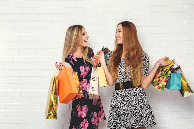 Hermosas chicas adolescentes llevando bolsas de compras