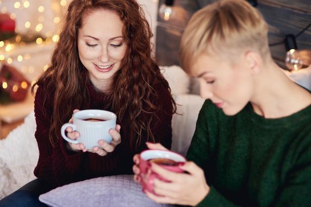 Hermosas chicas bebiendo té caliente con limón en día de invierno