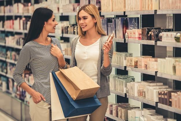 Hermosas chicas con bolsas de compras eligen perfumes