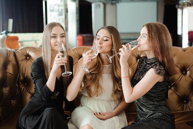 Hermosas chicas calientes divirtiéndose en la fiesta, bebiendo champán