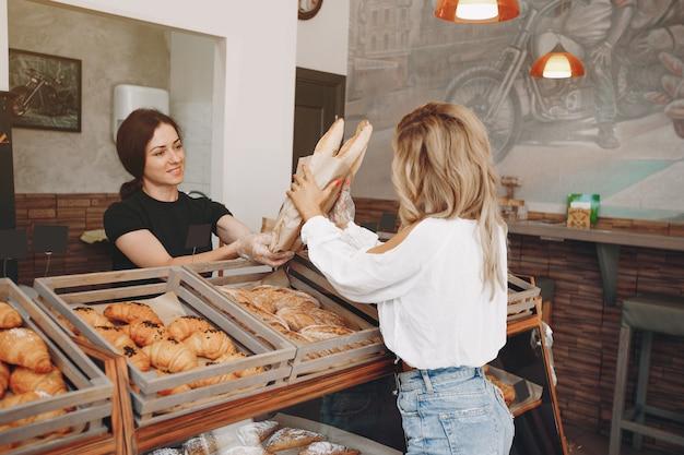 Hermosas chicas compran bollos en la panadería