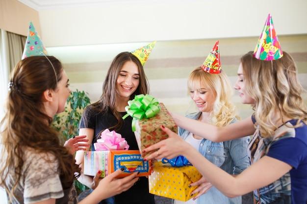 Hermosas chicas dan un regalo para el cumpleaños de su novia.