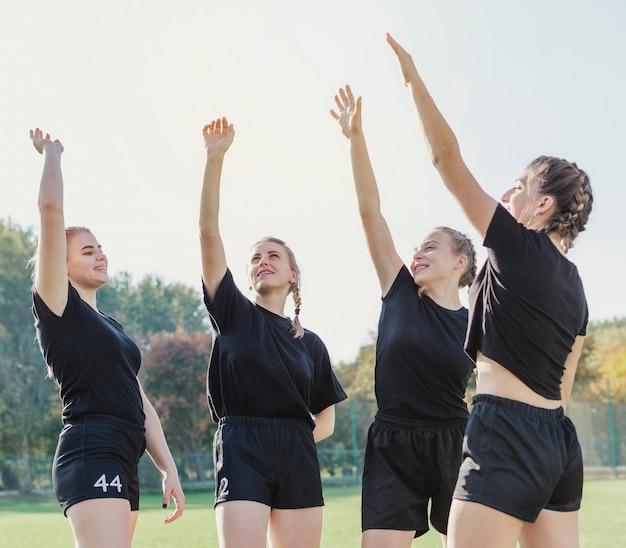Hermosas chicas deportivas levantando las manos