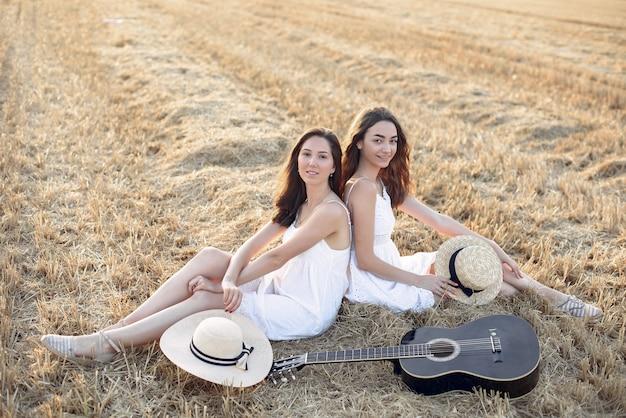 Hermosas chicas elegantes en un campo de trigo de otoño