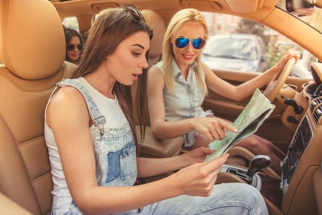 Hermosas chicas con estilo están estudiando el mapa.