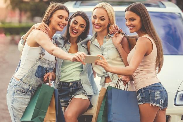 Hermosas chicas con estilo están haciendo selfie usando un teléfono inteligente.