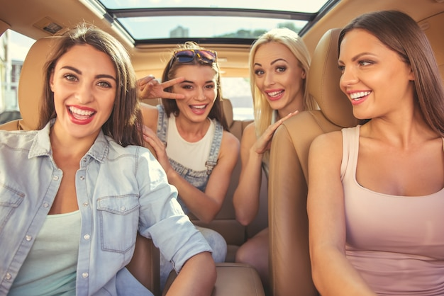 Hermosas chicas con estilo están mirando a la cámara.